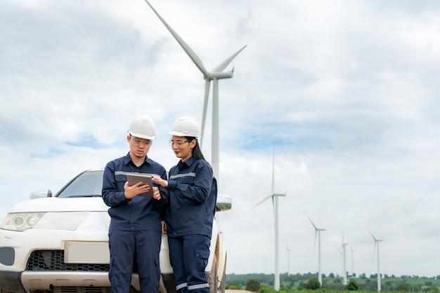 風力発電所での男性と女性の検査エンジニアの準備と進捗チェック