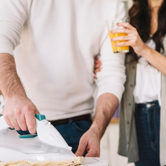 Мужчина и женщина, гладящие белье
