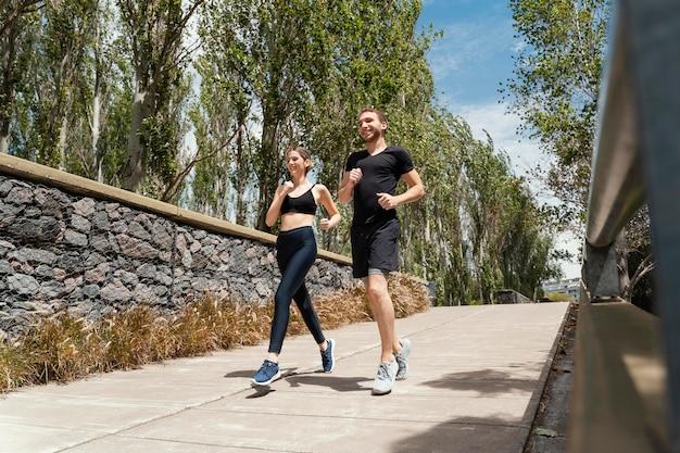 Мужчина и женщина бегают вместе на открытом воздухе