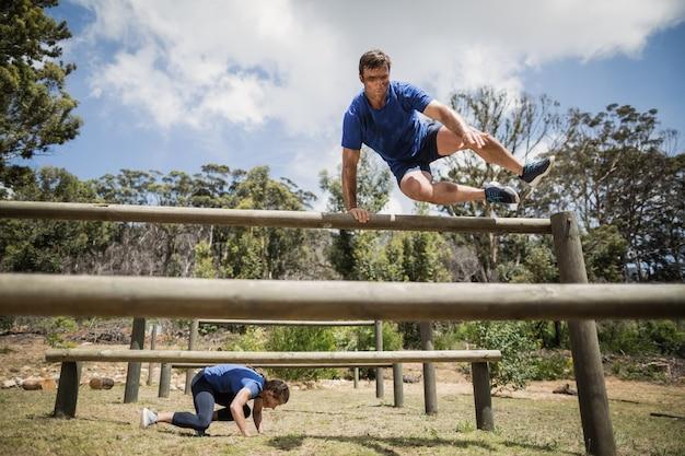 Мужчина и женщина перепрыгивают через препятствия во время полосы препятствий в учебном лагере