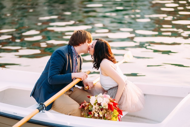 남자와 여자는 꽃다발 옆에 보트에서 키스