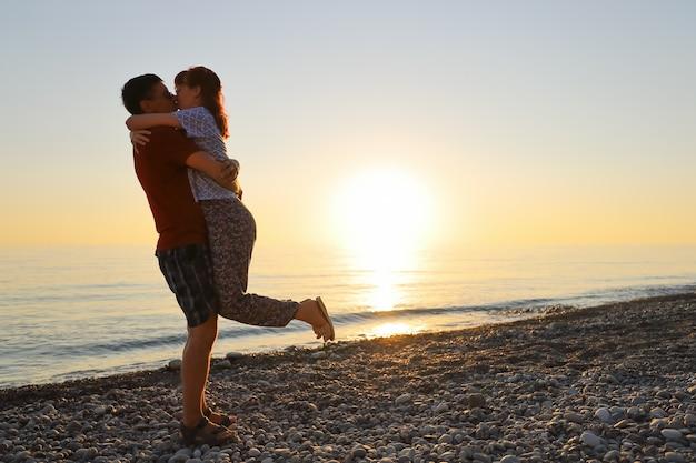 海のビーチの夕日で男と女が他の腕を抱きしめてキス