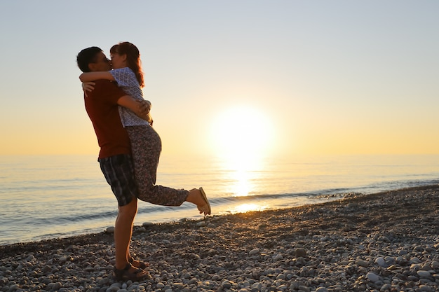 Мужчина и женщина целуются в объятия друг друга на закате морского пляжа
