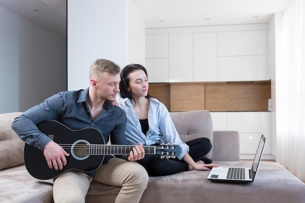 남자와 여자는 노트북을 사용하여 기타를 연주하는 법을 배우고, 젊은 부부는 집에서 함께 좋은 시간을 보내고 소파에 앉아