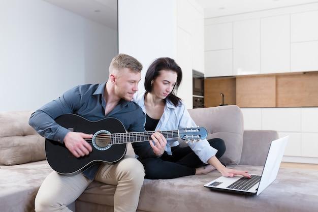 Мужчина и женщина учатся вместе играть на гитаре с помощью ноутбука, молодая пара хорошо проводит время вместе дома, сидя на диване