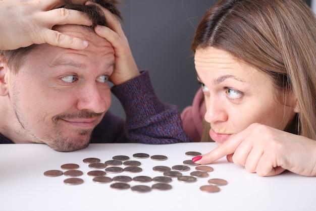 남자와 여자는 좌절감에 동전을 봅니다. 가족 예산 계획 개념