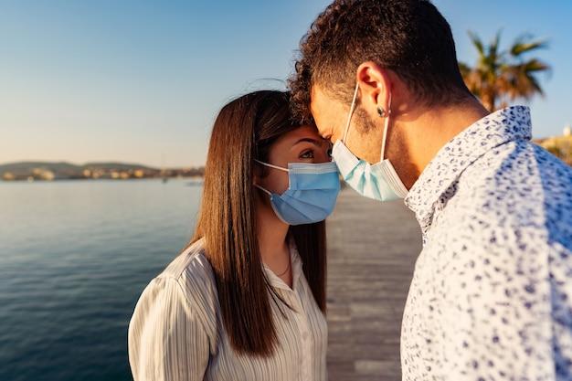 Мужчина и женщина смотрят друг другу в глаза, прислонившись лбом друг к другу в защитной маске из-за коронавируса.