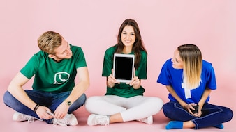 Man and woman looking at her happy female friend showing digital tablet