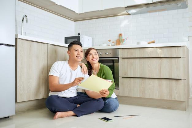 彼らの家の計画を見ている男性と女性は彼らの新しい家に座っています