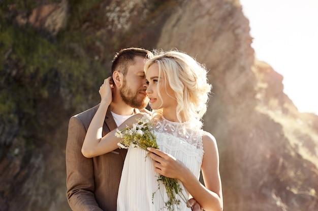 남자와 여자의 사랑과 포옹, 가까운 관계와 사랑, 강 근처의 바위에 사랑에 빠진 부부, 물 스프레이에 키스하고 껴안기