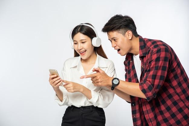 남자와 여자는 스마트 폰으로 음악을 듣는 것을 좋아합니다.