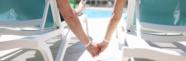 남자와 여자는 수영장 근처 일광욕 라운저에 누워 손을 클로즈업