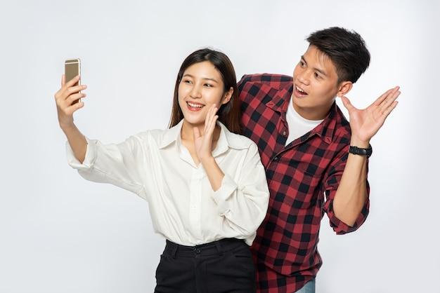 男性と女性がスマートフォンから自分撮りをからかう