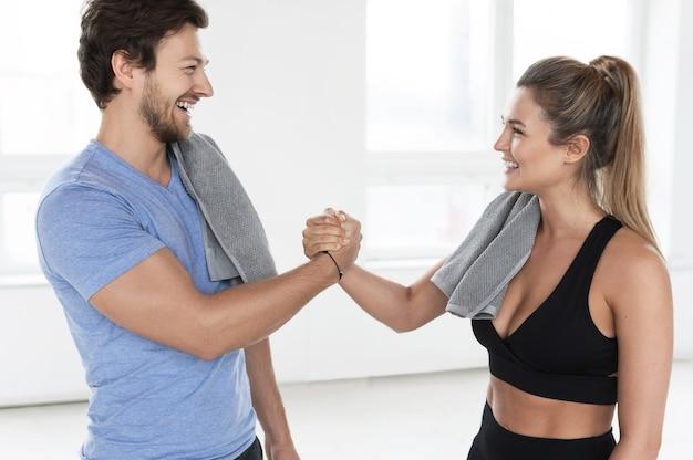 トレーニング後のジムでフレンドリーなアームレスリング握手をする男女。競争心、進歩、友情。