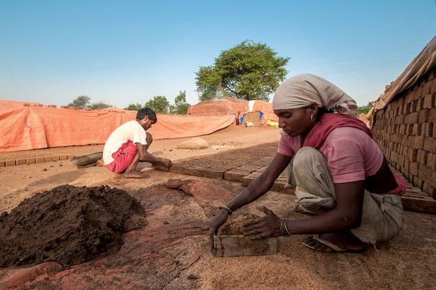 男と女のレンガ工場で粘土の伝統的なレンガを作る