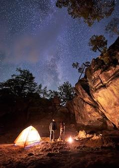Мужчина и женщина возле палатки и горящего огня