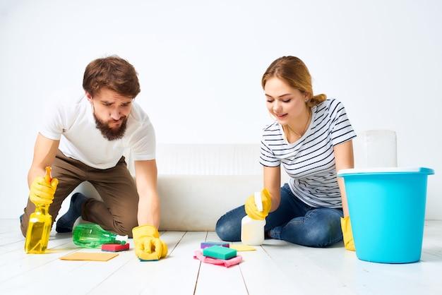 アパートの保護手袋のソファの掃除の近くの男と女