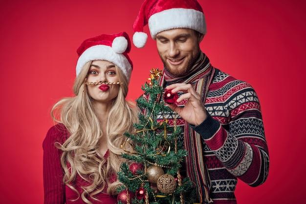 男性と女性の新年のお祝い一緒にクリスマスの赤い背景