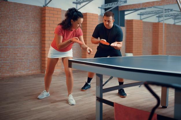 Мужчина и женщина на тренировке по настольному теннису
