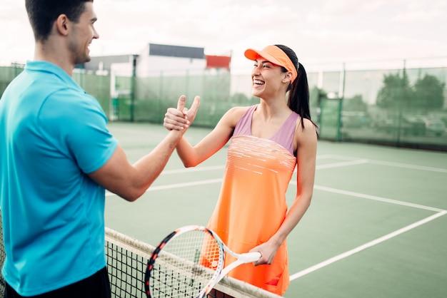 男性と女性のパートナーが屋外テニスコートに。夏季アクティブスポーツゲーム