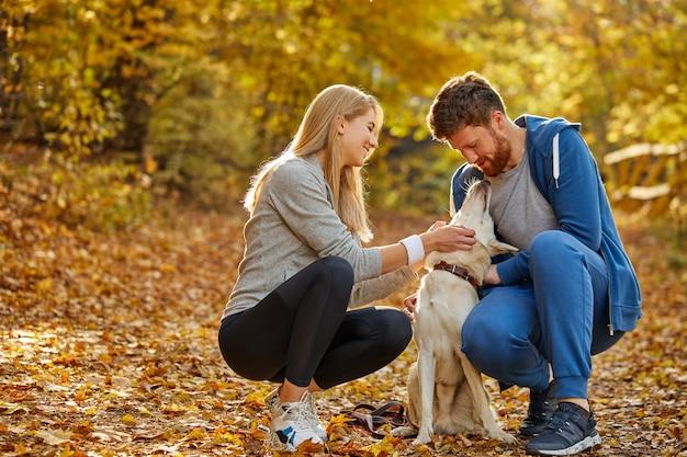 男と女は田舎の森で親切な白いペットの犬と遊ぶ
