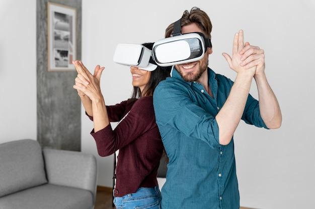 Мужчина и женщина вместе играют с гарнитурой виртуальной реальности дома