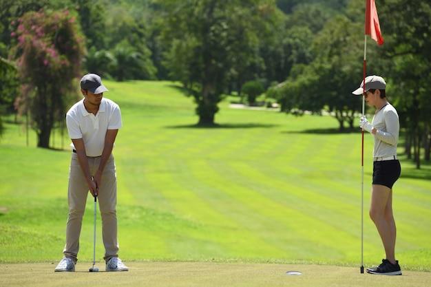 남자와 여자는 아름다운 자연 골프 코스에서 골프