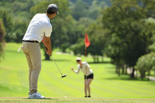 Мужчина и женщина играют в гольф на красивом естественном поле для гольфа