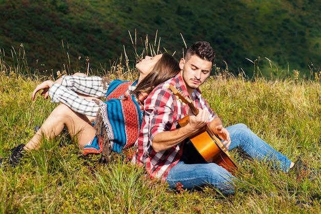 Мужчина и женщина играют на гитаре и поют на природе