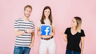 Man and woman pointing at their friend holding facebook icon on pink backdrop