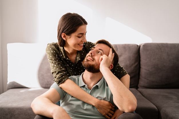 Мужчина и женщина портрет, улыбаясь друг другу на диване