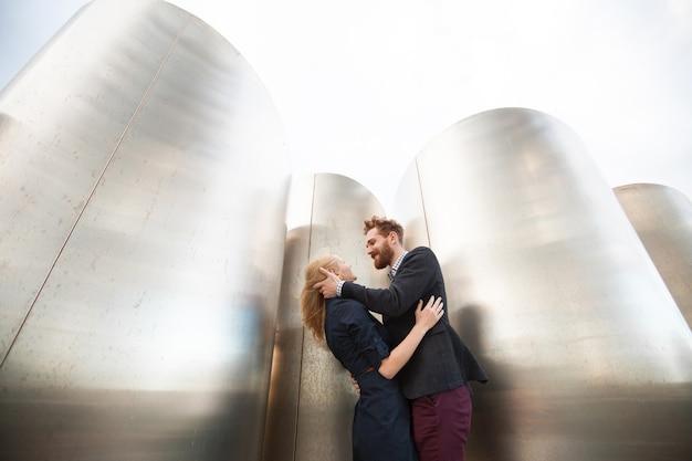 Мужчина и женщина позируют перед большими металлическими трубами