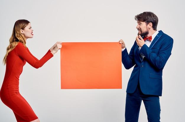 男と女がお互いに赤いモックアップポスター広告販売を引っ張る。高品質の写真