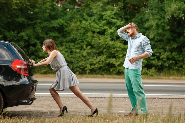 Мужчина и женщина толкают разбитую машину на дороге, поломка.