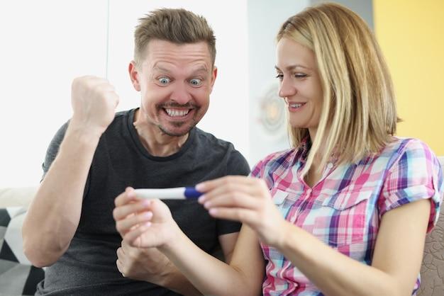 남자와 여자는 기뻐하고 집에서 긍정적 인 임신 테스트를 개최