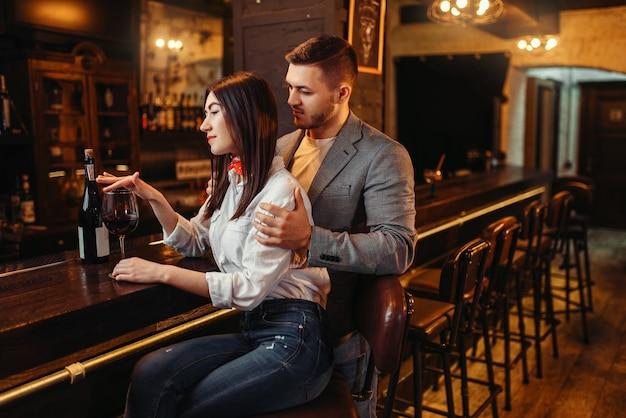 男性と女性がリラックスし、木製のバーカウンターでカップル。パブでの恋人のレジャー、ナイトクラブで一緒にリラックスする夫と妻