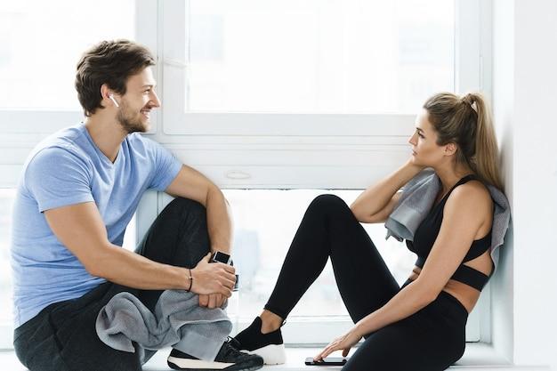 ジムでのフィットネストレーニングの後に休んでいる男性と女性