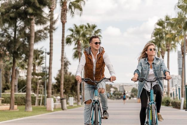 Мужчина и женщина, езда на велосипедах снаружи