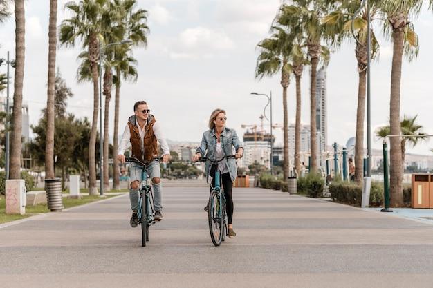 Мужчина и женщина вместе едут на велосипедах