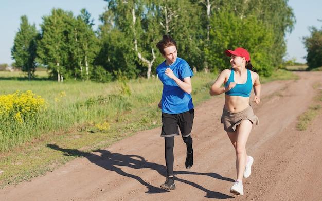男と女は、晴れた夏の夜、森を背景に田舎道を走り、笑顔を浮かべる。側面図