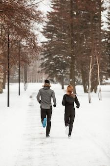 Мужчина и женщина, бегущие в лесу полный выстрел