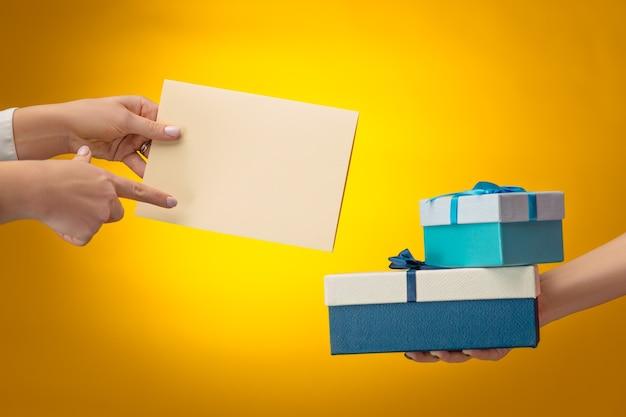 Руки мужчины и женщины с подарочной коробкой на желтом фоне с копией пространства на пустом бланке