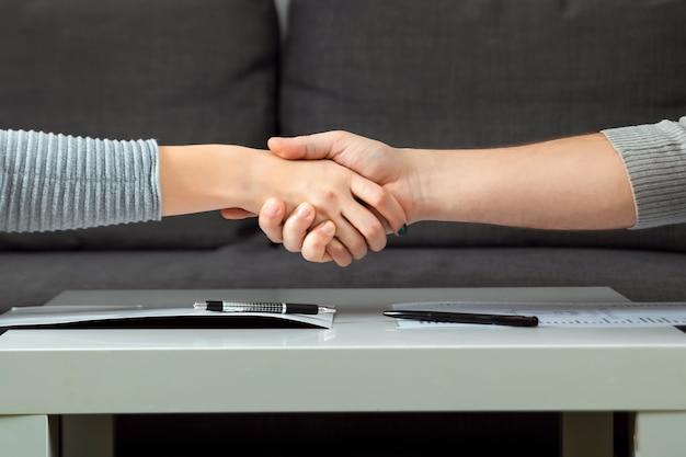 Мужчина и женщина пожать друг другу руки крупным планом. семейная ссора, разборки, раздел имущества, развод