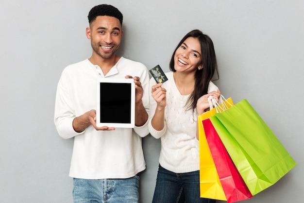 男と女のクレジットカードと空の画面とタブレットを表示