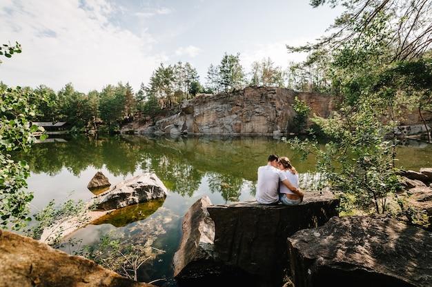 男と女は大きな岩の表面にある湖の近くの石に座って抱きしめます