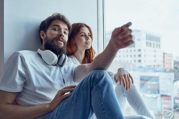 男と女はヘッドフォンロマンスの喜びで窓の近くに座っています
