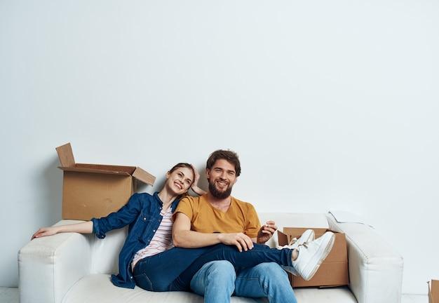 Мужчина и женщина сидят на белых диванных ящиках с движущимися предметами образа жизни