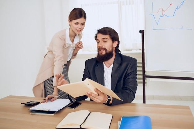 Мужчина и женщина сидят за столом в офисе, работают технологии коммуникации