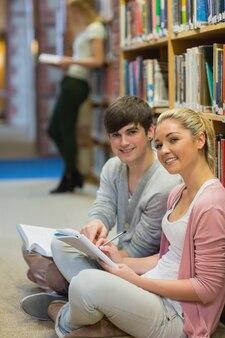 男性と女性が笑いながら本棚の前に座っている