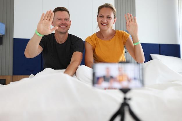 Мужчина и женщина сидят в постели отеля и машут рукой на камеру мобильного телефона
